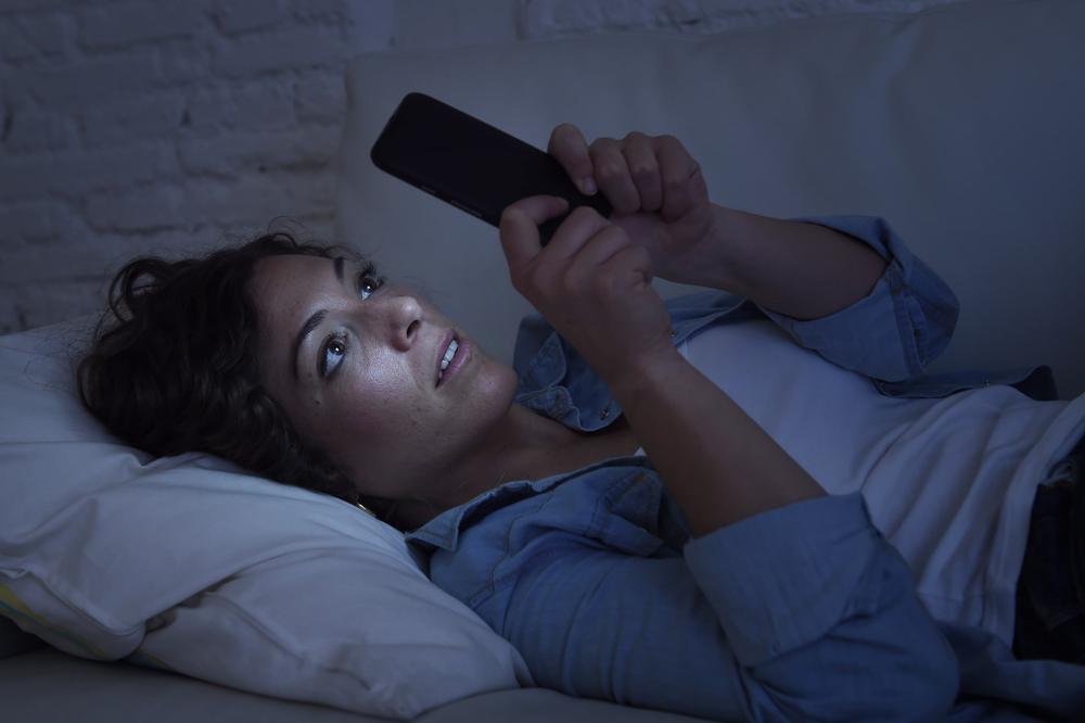 mulher vendo celular na cama